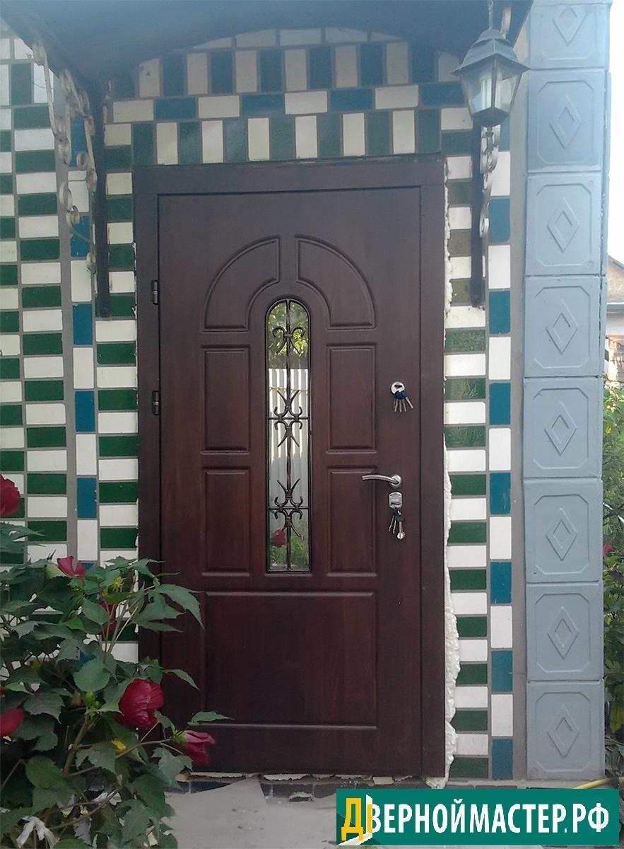 Классическая модель наружной уличной двери для частного дома с окошком и ковкой.