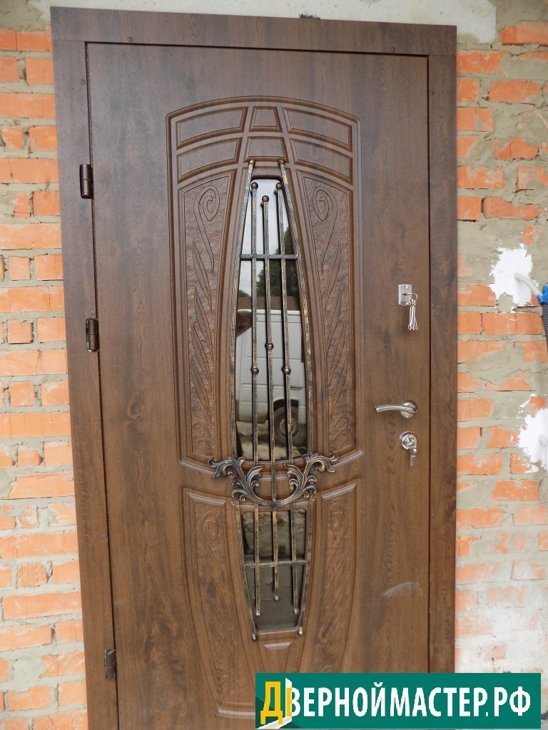Оригинальная модель входной двери в частный дом со стеклом и декоративной кованой решеткой